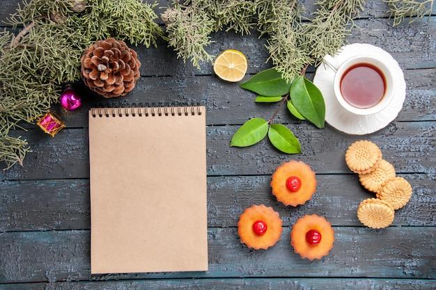 Vista dall'alto cupcakes ciliegia rami di abete fetta di limone una tazza di biscotti da tè e un taccuino sulla tavola di legno scuro