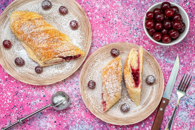Вид сверху вишневое тесто вкусное и сладкое, нарезанное свежей вишней внутри тарелок на цветном столе, печенье, сахар, сладкая выпечка