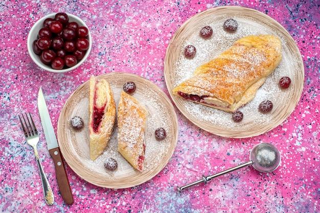 Вид сверху вишневое тесто вкусное и сладкое, нарезанное свежей вишней внутри тарелок на цветном письменном торте, печенье, сахар, сладкая выпечка