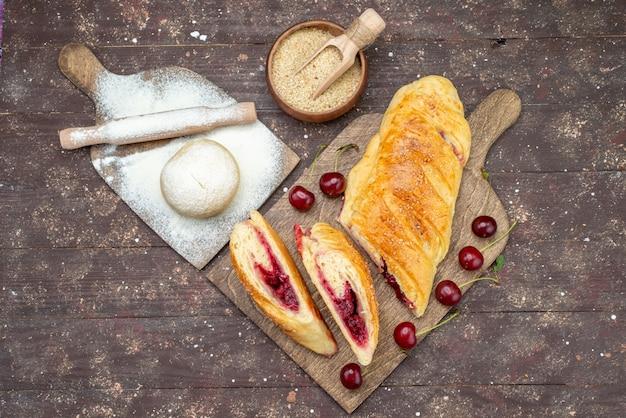 Вид сверху вишневое тесто вкусное и сладкое со свежей вишней на коричневом деревянном столе кондитерский торт бисквит сладкая выпечка фрукты