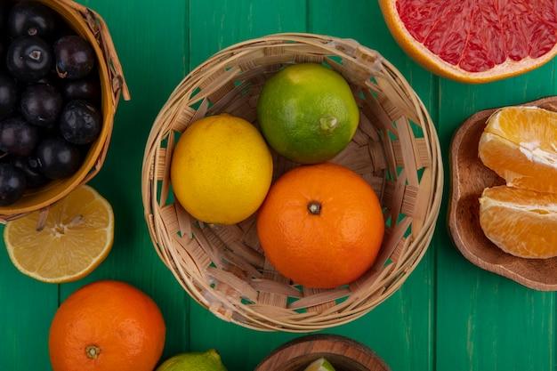 Vista dall'alto ciliegia prugna in un cesto con limone arancia e lime in un cesto su uno sfondo verde
