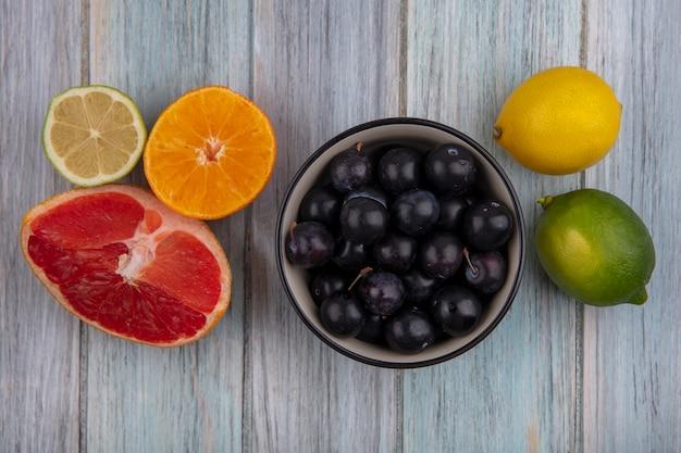 Vista dall'alto prugna ciliegia in una ciotola con spicchi di pompelmo arancia e limone e lime su sfondo grigio