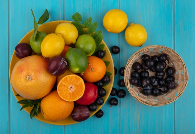 ターコイズブルーの背景の黄色いプレートにオレンジとライムのレモンとバスケットのチェリープラムの上面図