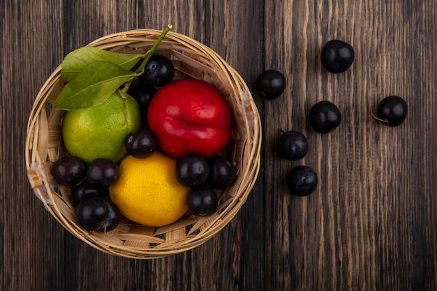 木製の背景の上のバスケットにレモンライムと桃とチェリープラムの上面図