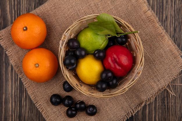 Vista dall'alto ciliegia prugna con limone lime e pesca in un cesto con arance su un tovagliolo beige