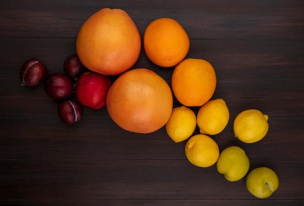Вид сверху алычи с лимонами, апельсинами, грейпфрутом и персиком на деревянном фоне