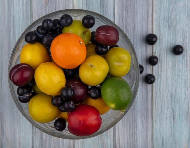 灰色の背景にオレンジ色のレモンとフルーツの花瓶にライムとチェリープラムの上面図