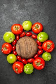 Вид сверху вишнево-красные и зеленые помидоры вокруг деревянной тарелки на темной земле со свободным пространством