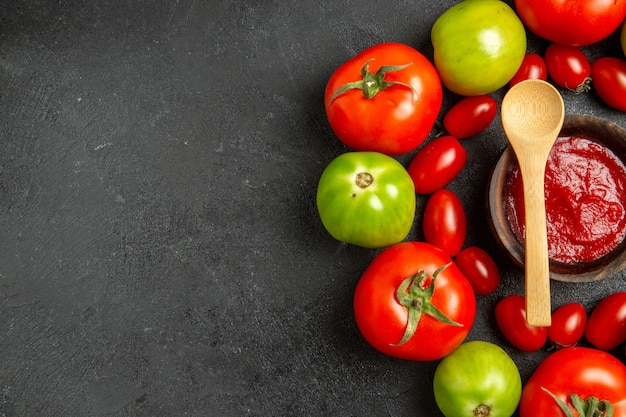 Top view cherry red and green tomatoes around a bowl with ketchup and a wooden spoon on dark table with copy space