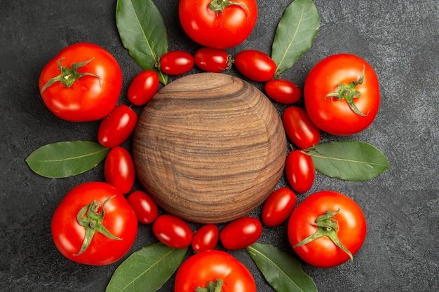 Vista dall'alto di pomodori ciliegia e foglie di alloro rosso intorno a un piatto di legno su fondo scuro
