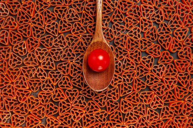 Top view cherry tomato on spoon on red hearts italian pasta on dark table