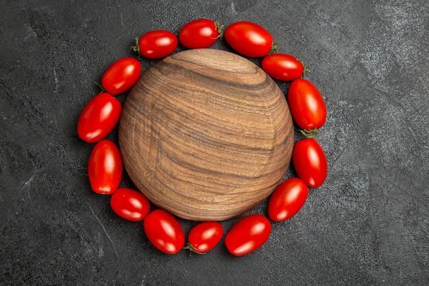 Pomodori ciliegia vista dall'alto intorno a un piatto di legno su fondo scuro con spazio di copia