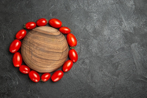 Vista dall'alto pomodorini intorno a un piatto di legno a sinistra del terreno scuro con spazio di copia