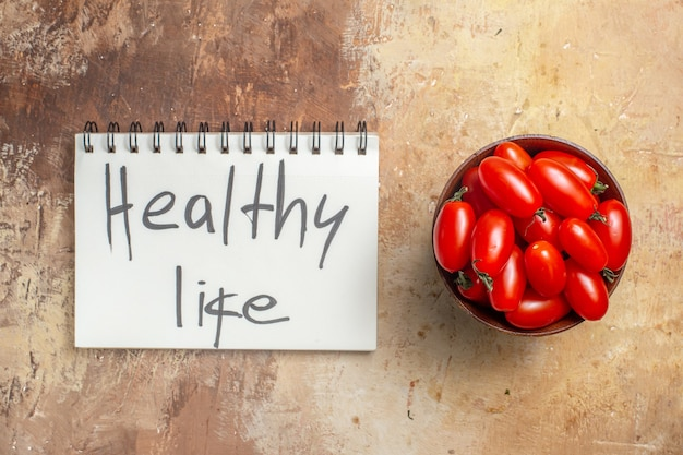 Вид сверху помидоров черри в деревянной миске здорового образа жизни, написанного в блокноте на янтарном фоне