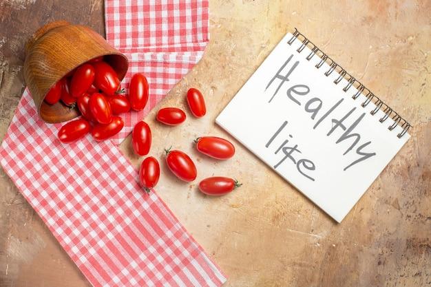 Vista dall'alto pomodorini sparsi dalla ciotola un asciugamano da cucina vita sana scritta su un quaderno su sfondo ambra