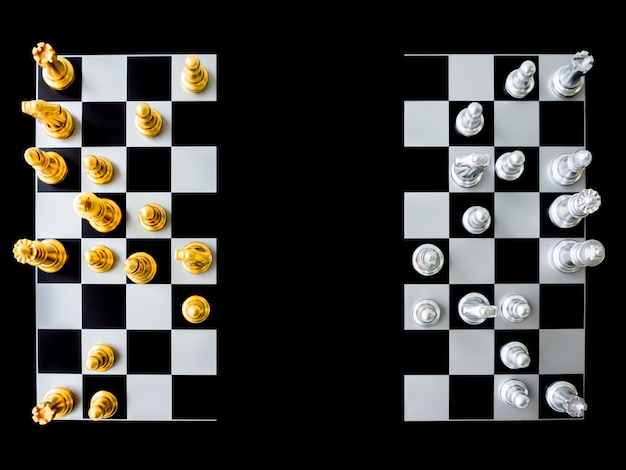 Top view of chess and  chessboard is divided in half on a black background.