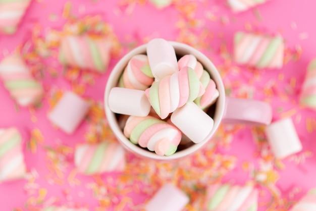 Una vista dall'alto che mastica marshmallow all'interno della tazza rosa e tutto sulla scrivania rosa
