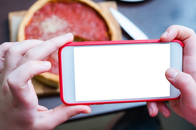 Top view of chicago pizza. woman hands taking photo with smart phone of chicago style deep dish italian cheese pizza with tomato sauce and beef meet inside. blank, empty screen