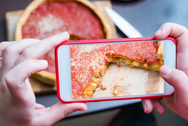 Top view of chicago pizza. woman hands taking photo with smart phone.