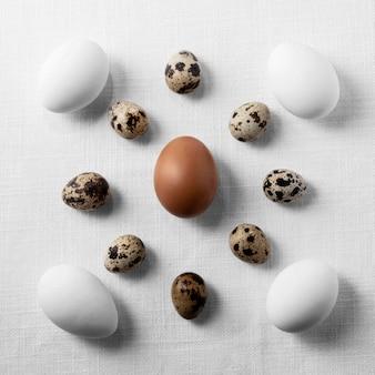Вид сверху куриные и перепелиные яйца на столе