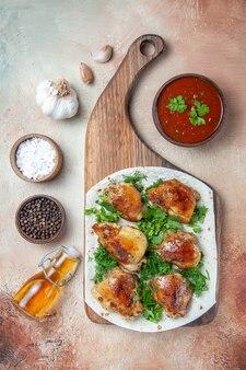Vista dall'alto della ciotola di pollo di salsa di spezie olio di pollo con erbe su lavash sulla lavagna