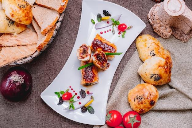 Вид сверху рулет из куриной грудки с соусом из помидоров и хлеба