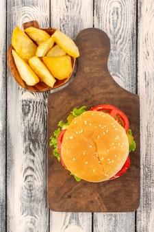 Un hamburger di pollo con vista dall'alto con formaggio e patate con insalata verde