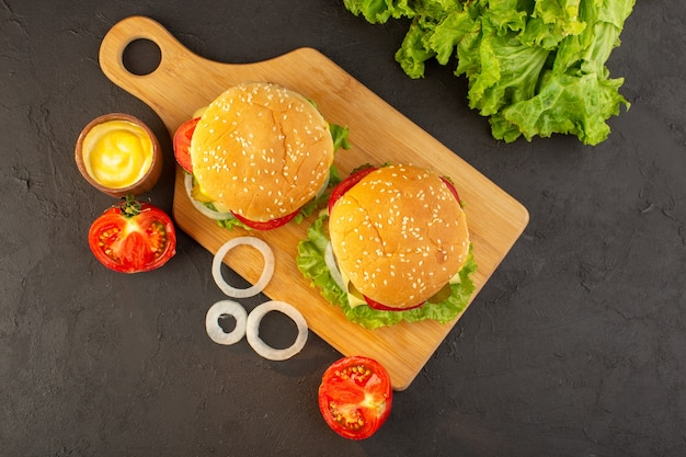 A top view chicken burger with cheese and green salad