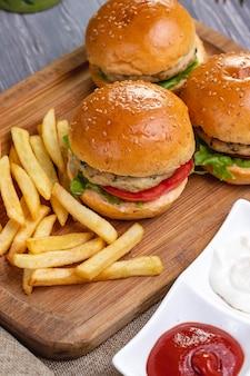 トップビューチキンハンバーガーとボード上のフライドポテトケチャップとマヨネーズ