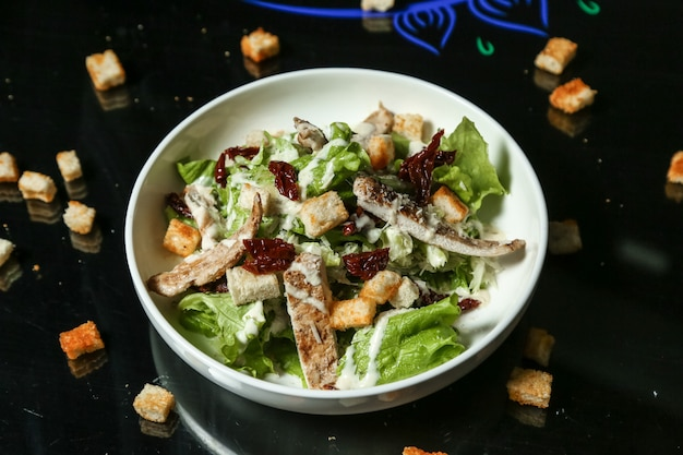 Top view chicken caesar salad with croutons on the table