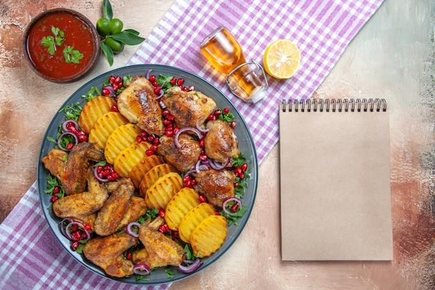 灰色のノートの横にあるテーブルクロスの上面図チキンチキンウィングポテトレモンオイル