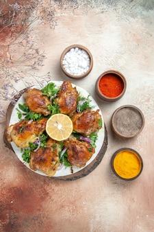 Vista dall'alto di pollo pollo con erbe aromatiche al limone sul tagliere spezie in ciotole