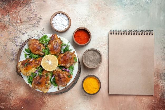 Vista dall'alto di pollo pollo con spezie erbe limone in ciotole accanto al taccuino crema