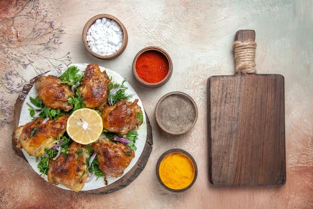 Vista dall'alto di pollo pollo con erbe aromatiche al limone spezie in ciotole accanto al tagliere