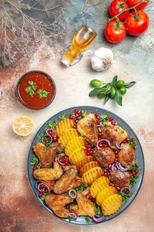 Vista dall'alto di pollo pollo con patate olio spezie pomodori salsa aglio limone