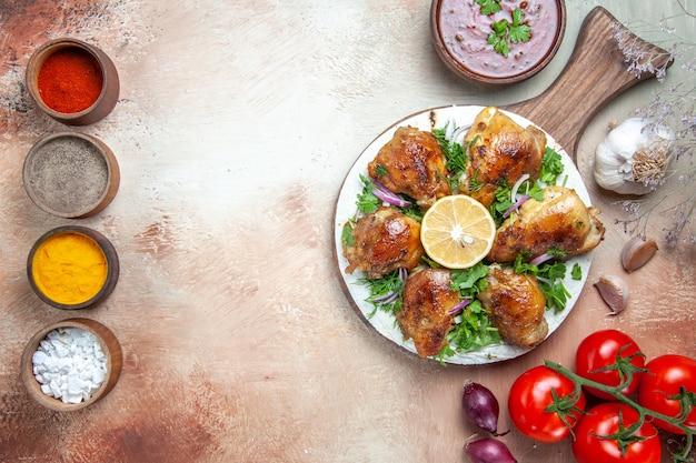 Vista dall'alto di pollo salsa di spezie colorate pollo con erbe cipolla pomodori con peduncoli
