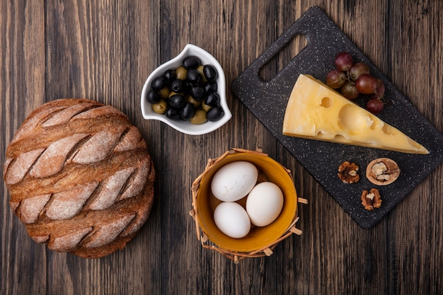 Top view chicken eggs in a basket of olives in a saucer with maasdam cheese on a stand with black bread on a wooden background