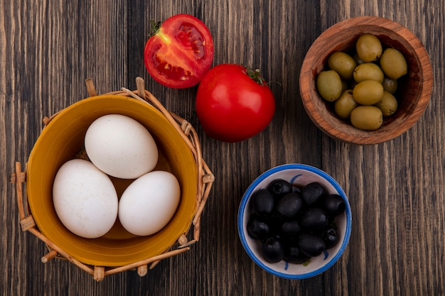 Top view chicken eggs in basket with black and green olives in bowls and tomatoes on wooden background
