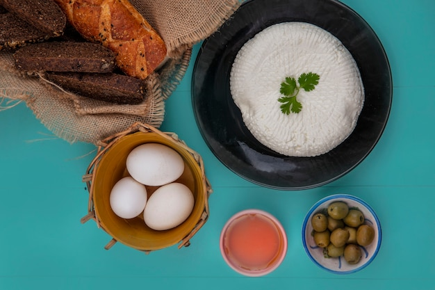 Top view chicken eggs in a basket with cheese  olives and black bread on a turquoise background