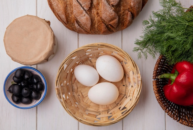 Top view chicken eggs in basket with olives  yogurt  loaf of bread  with dill on white background