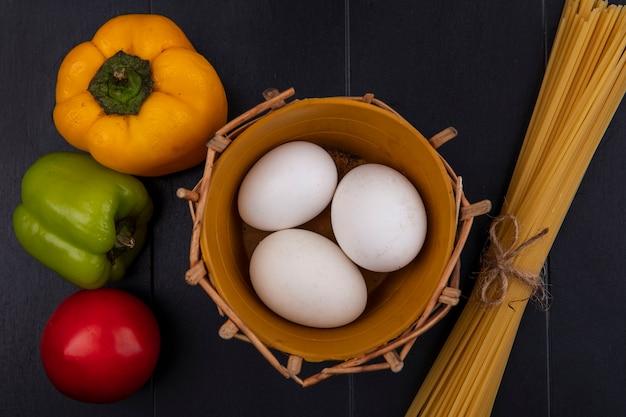 Uova di gallina vista dall'alto nel cestino con spaghetti crudi e peperoni su sfondo nero