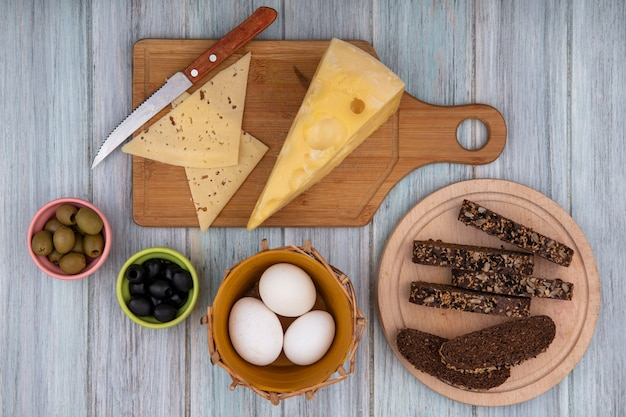Top view chicken eggs in a basket with slices of black bread on a stand with cheeses on a cutting board and a knife  on a gray background