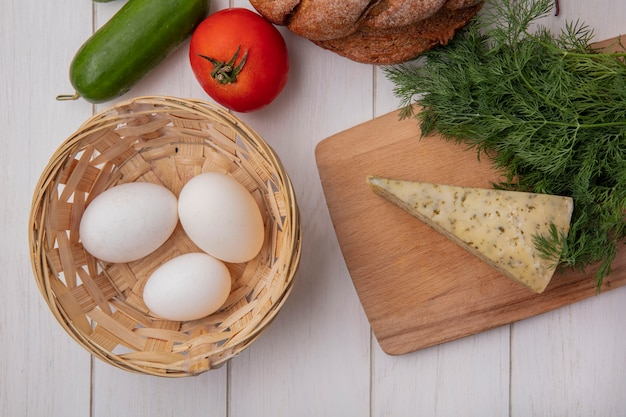 Top view chicken eggs in a basket with tomato  cucumber and a loaf of black bread with cheese and dill  on white background