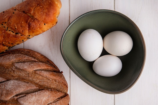 Top view chicken eggs in bowl and loaf of black and white bread on white background