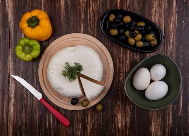 Vista dall'alto le uova di gallina in una ciotola con formaggio feta su un supporto con peperone e bolivi su uno sfondo di legno