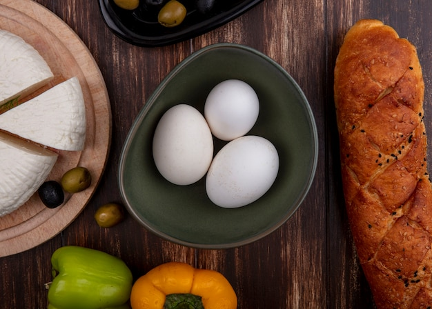 Top view chicken eggs in bowl with feta cheese on stand with bell pepper and loaf of bread on wooden background