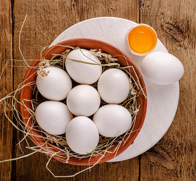Top view of chicken eggs in bowl with hay on wooden table