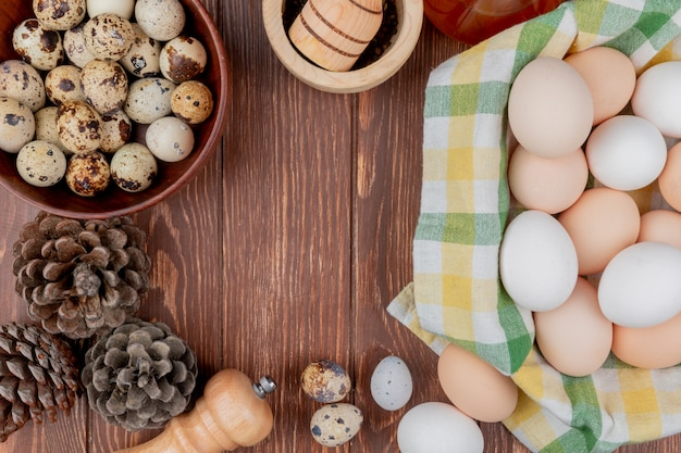 Top view of chicken eggs on a checked tablecloth and quail eggs on a bowl with pine cones isolated on a wooden background