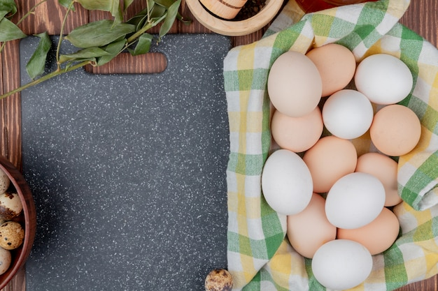 Top view of chicken eggs on a checked tablecloth with quail eggs on a wooden bowl with leaves on a wooden background with copy space