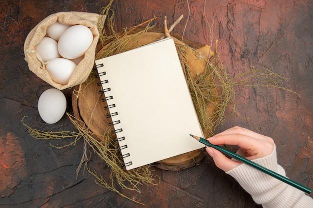 Vista dall'alto uova di gallina all'interno di una piccola borsa, scrittura a mano su un taccuino vuoto